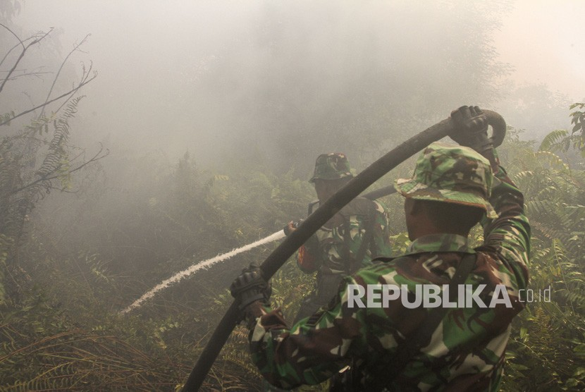TNI officers tried to extinguish land fires in the midst of thick smoke in Pekanbaru, Riau.