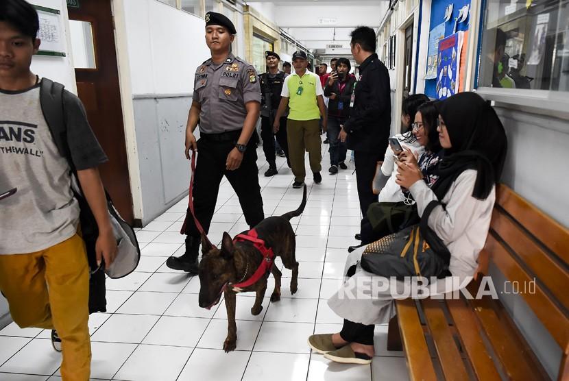 Petugas unit K9 Polda Metro Jaya (unit keamanan dengan bantuan anjing pelacak) merazia narkoba saat gelar patroli cipta kondisi gabungan P4GN di Universitas Nasional, Jakarta, Selasa (25/6/2019).