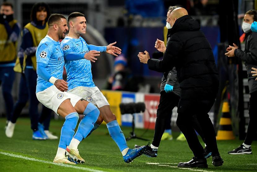 Phil Foden (C) merayakan golnya bersama pelatih Manchester City Pep Guardiola (R). Golnya membuat City unggul 2-1 pada leg kedua perempat final Liga Champions melawan Dortmund, Kamis (15/4).