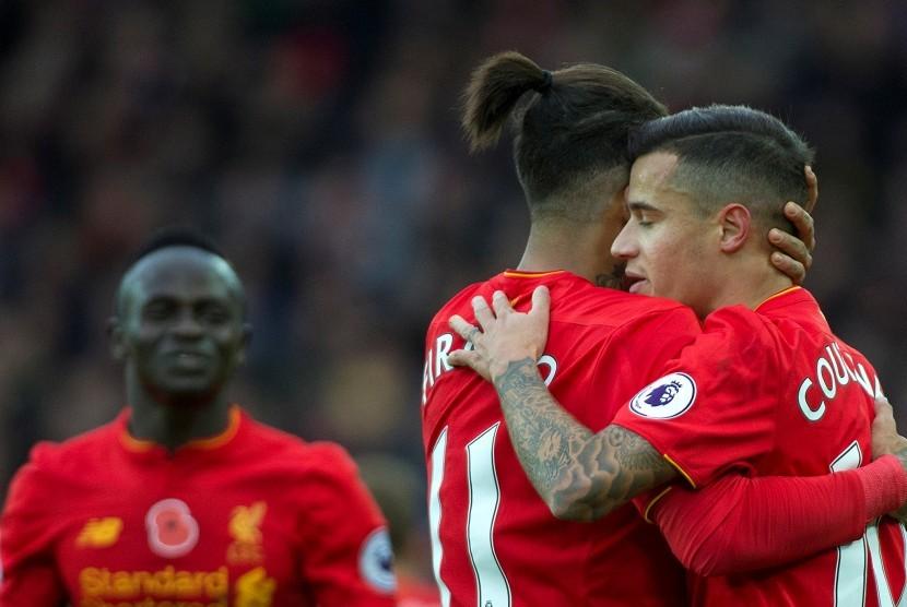 Philippe Coutinho mendapatkan selamat dari Roberto Firmino seusai mencetak gol ke gawang Watford, akhir pekan lalu. Liverpool kini berada di puncak klasemen Liga Primer Inggris.