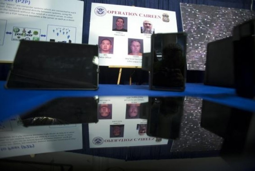 Photos of people arrested in a sting operation are reflected in a seized tablet computer following a news conference to announce the arrest of 71 individuals for sharing child pornography online in New York May 21, 2014.