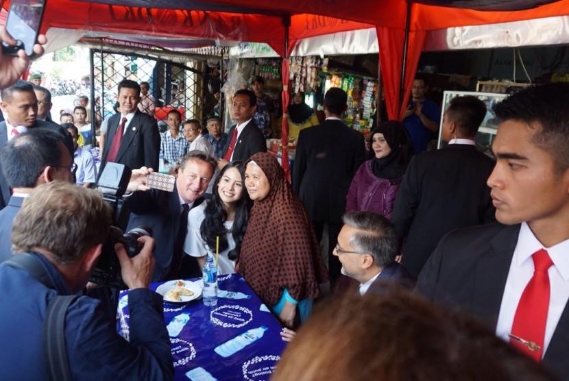 PM Inggris David Cameron melakukan selfie dan memakan pisang goreng di pedagang kaki lima di depan Masjid Sunda Kelapa, Selasa (28/7).