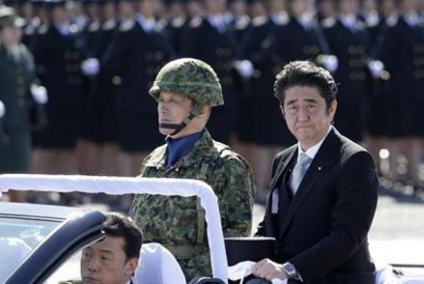 PM Jepang Shinzo Abe (mengenakan jas) melakukan inspeksi terhadap pasukan Bela Diri Jepang dalam peringatan Hari Bela Diri di Pangkalan Asaka, Tokyo.