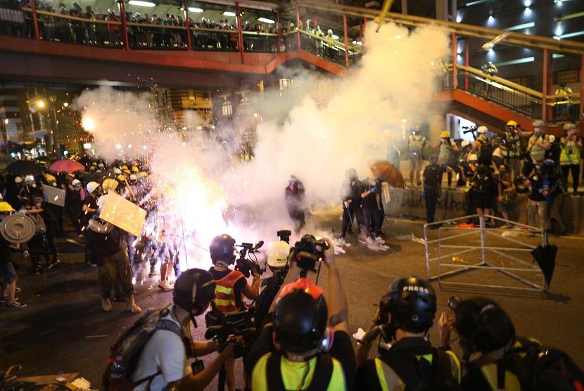 Polisi Anti Huru Hara menembakkan gas air mata kepada demonstran yang melakukan kampanye di Hong Kong, Ahad (21/7)