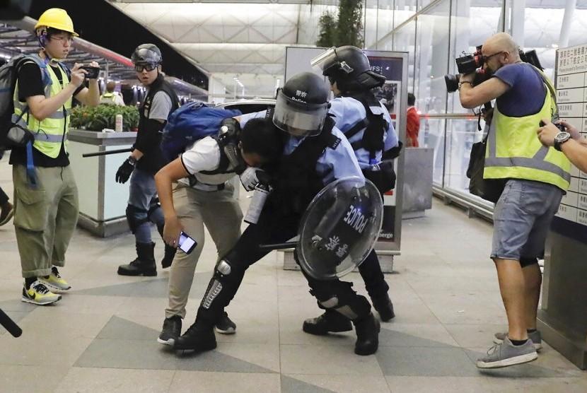 Polisi antihuru-hara Hong Kong menahan seorang demonstran di Bandara Internasional Hong Kong, Selasa (13/8).