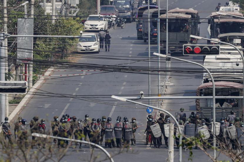 Polisi berdiri dalam formasi memblokir jalan utama di Mandalay, Myanmar, Sabtu, 27 Februari 2021. Pasukan keamanan Myanmar menindak pengunjuk rasa anti-kudeta di kota terbesar kedua negara itu, Mandalay, pada hari Jumat, melukai sedikitnya tiga orang, dua dari ada yang ditembak di bagian dada dengan peluru karet dan satu lagi yang mengalami luka di kaki.