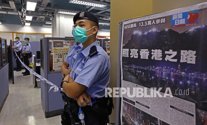 Polisi berjaga di samping halaman depan surat kabar Apple Daily