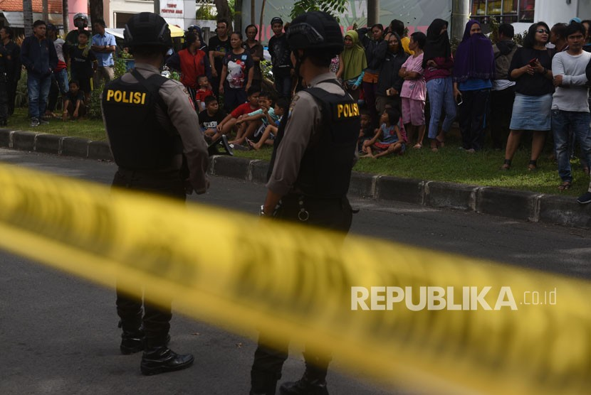 Polisi berjaga saat berlangsung penggeledahan di rumah terduga teroris di kawasan Dukuh Pakis, Surabaya, Jawa Timur, Kamis (17/5).