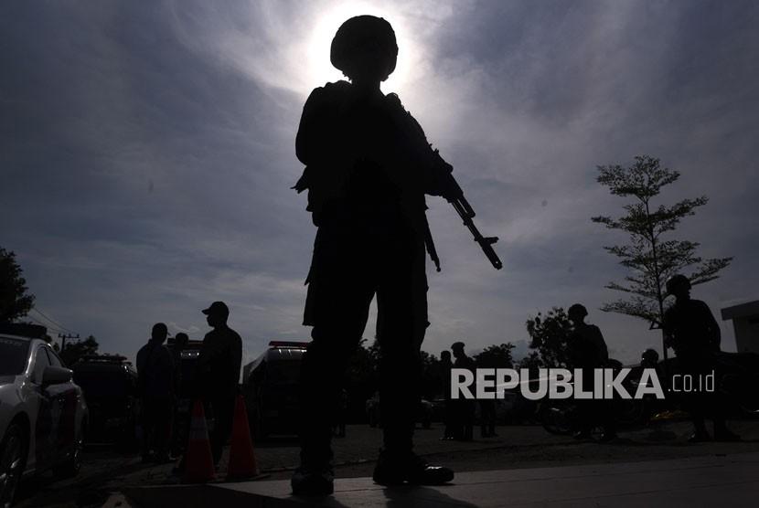 Polisi berjaga saat pemindahan jenazah terduga pelaku teror dari ruang pendingin ke ambulans di RS Bhayangkara, Surabaya, Jawa Timur, Jumat (18/5).