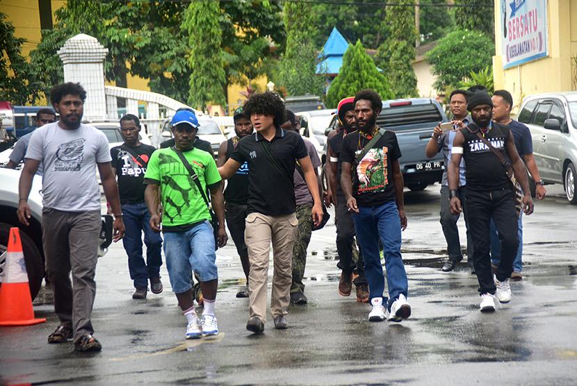 Polisi berpakaian preman berjalan bersama sepuluh anggota Tentara Pembebasan Nasional (TPN) Organisasi Papua Merdeka (OPM) di Markas Polda Papua, beberapa waktu lalu.