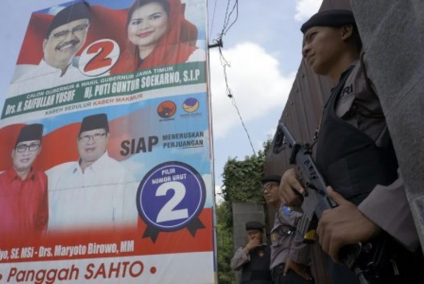 Polisi bersenjata berjaga saat digelarnya operasi penggeledahan oleh KPK di depan pintu gerbang rumah calon bupati pejawat Tulungagung Syahri Mulyo, di Ngantru, Tulungagung, Jawa Timur, Sabtu (9/6). Penggeledahan itu dilakukan untuk mencari bukti tambahan atas keterlibatan Syahri itu dalam dugaan korupsi proyek peningkatan infrastruktur jalan tahun 2017 yang saat ini tengah disidik KPK.