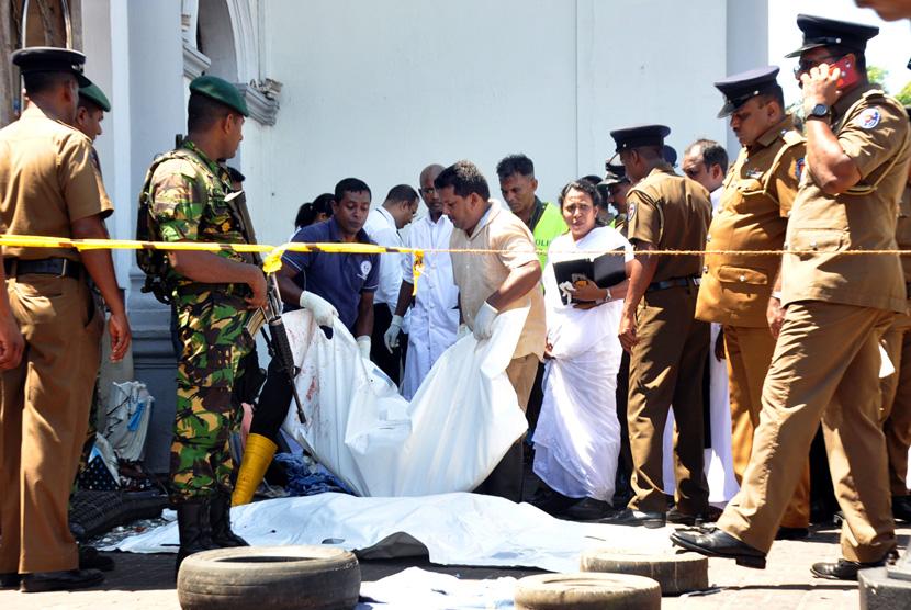 Polisi dan pekerja penyelamat memeriksa sisa-sisa korban di tempat kejadian setelah ledakan di Gereja St Anthony di Kochchikade di Kolombo, Sri Lanka, Ahad (21/4/2019).