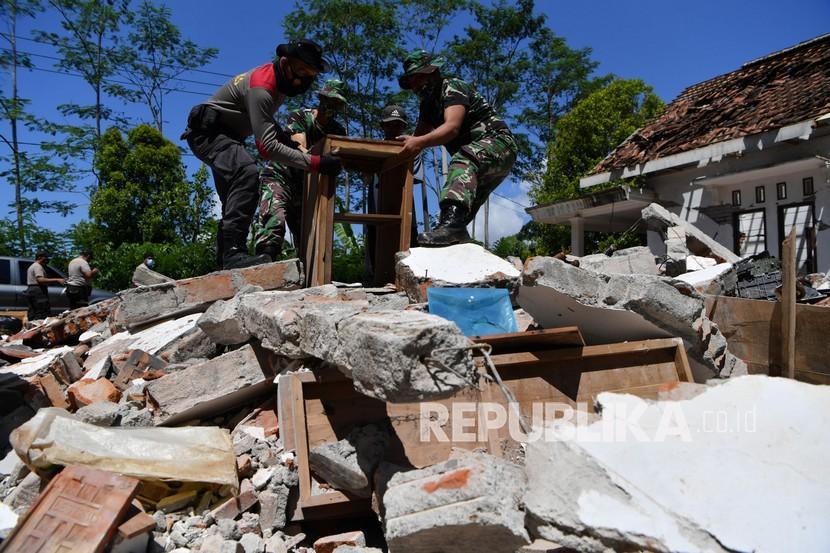 Polisi dan prajurit TNI AD membantu warga membersihkan puing-puing bangunan yang rusak akibat gempa di Desa Kaliuling, Lumajang, Jawa Timur, Senin (12/4/2021). Personel TNI dan Polri dikerahkan untuk membantu warga korban gempa untuk membersihkan sisa-sisa puing bangunan yang rusak akibat gempa.