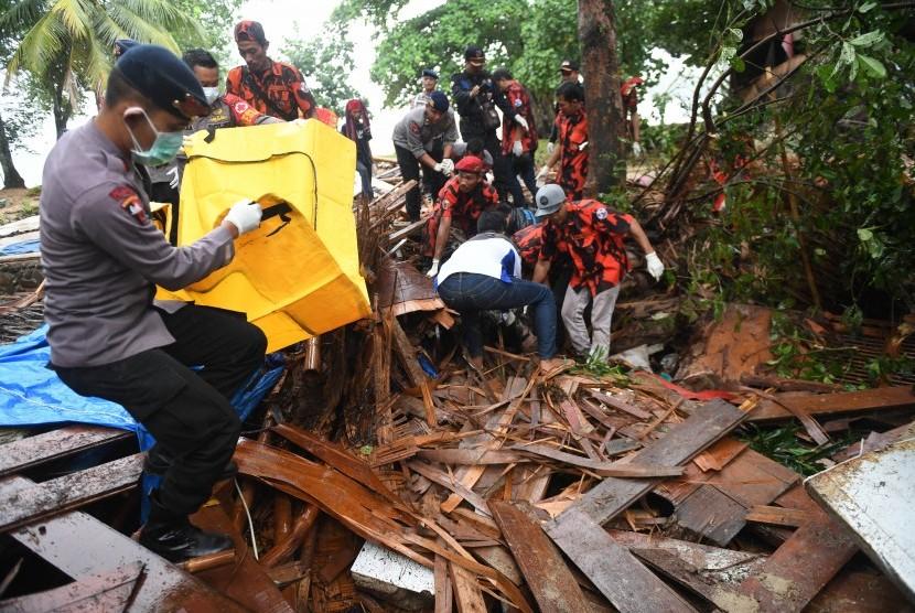 Polisi dan relawan mengevakuasi korban tewas akibat Tsunami yang tertimbun di bawah reruntuhan di kawasan Carita, Banten, Senin (24/12/2018).