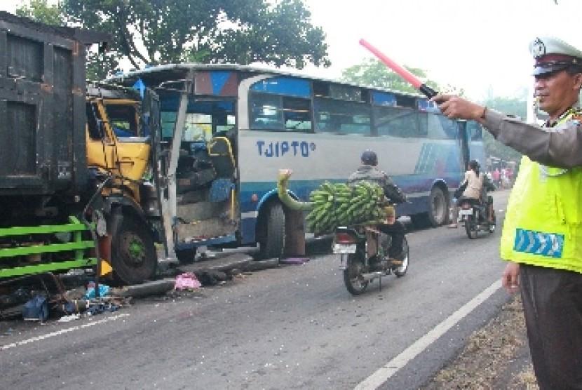Polisi lalu lintas mengatur jalan di sebelah bus yang terguling.