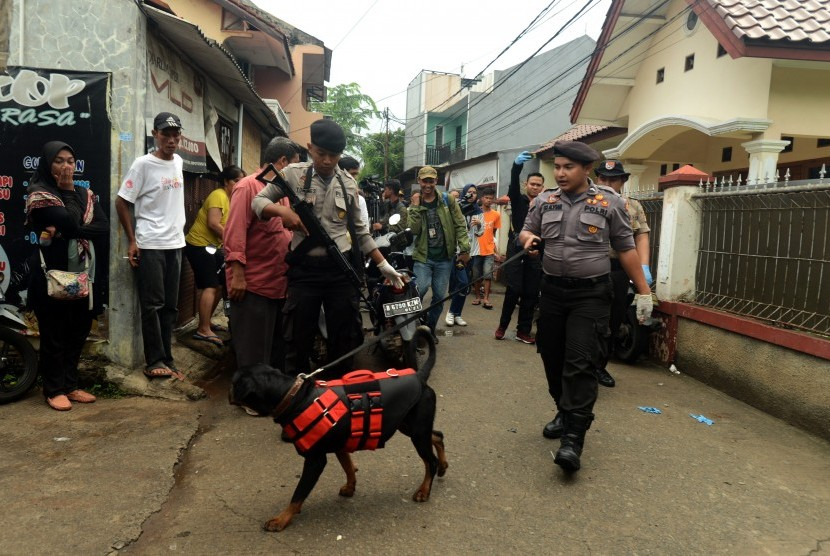 Polisi melakukan penyisiran dengan anjing pelacak di sekitar lokasi perisitiwa pembunuhan satu keluarga, di kawasan Jatirahayu, Bekasi, Jawa Barat, Selasa (13/11/2018). Dalam peristiwa tersebut satu keluarga yang terdiri empat orang tewas dengan luka di tubuhnya, motif penyebab masih dalam penyelid ikan pihak berwenang.