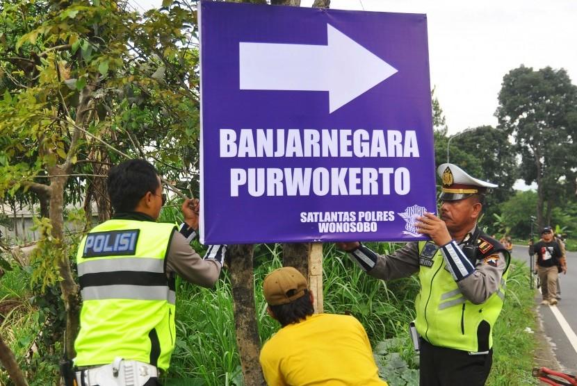Polisi memasang papan penunjuk arah di pinggir jalan raya Wonosobo-Temanggung-Magelang di jalur mudik poros tengah Kertek, Wonosobo, Jawa Tengah, Selasa (13/6).