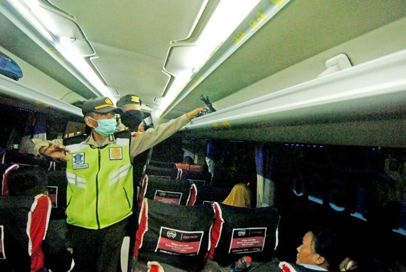 Polisi memeriksa barang bawaan penumpang bus saat razia penyekatan massa di jalur Pantura, Maribaya, Kabupaten Tegal, Jawa Tengah, Minggu (19/5/2019) malam.