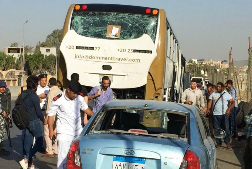 Polisi memeriksa sebuah mobil dan bus yang rusak akibat bom di Kairo, Mesir, Ahad (19/5). Sebuah bom meledak mengenai bus turis asing dekat Piramida Giza.