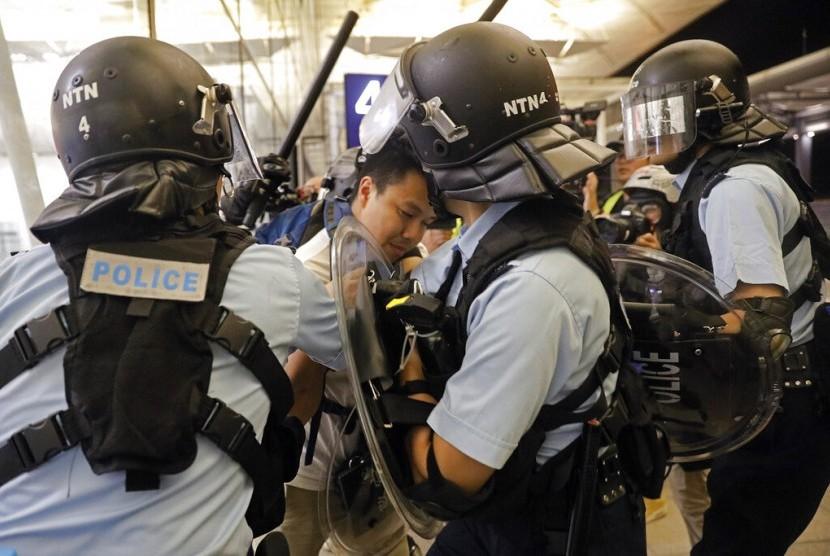 Polisi menahan seorang demonstran di Bandara Internasional Hong Kong, Selasa (13/8).