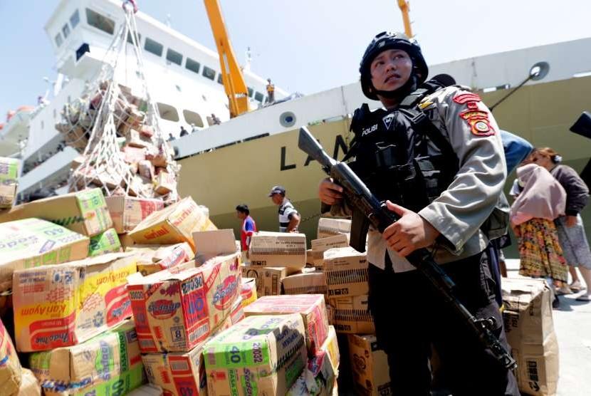Polisi mengamankan aktivitas bongkar muat bantuan makanan untuk korban gempa dan tsunami Palu serta Donggala di Pelabuhan Kelas-III Pantoloan, Palu, Sulawesi Tengah, Senin (1/10).