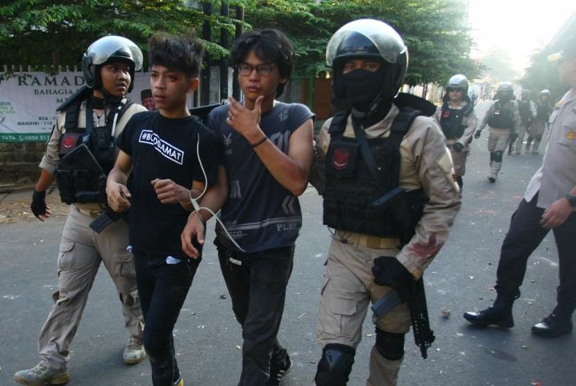 Polisi mengamankan dua orang yang diduga sebagai provokator saat terjadinya kerusuhan di atas jalan layang Slipi Jaya, Jakarta, Rabu (22/5/2019).