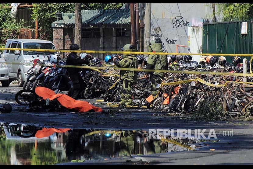 Polisi mengamankan lokasi parkir sepeda motor tempat ledakan bom terjadi di Gereja Pantekosta, Surabaya, Ahad (13/5)