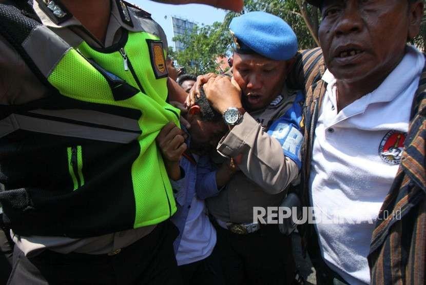 Polisi mengamankan seorang pemuda dari amukan massa saat aksi yang melibatkan dua kubu yang mendeklarasikan #2019 Ganti Presiden dan kubu yang menentang dan menyerukan cinta NKRI, di Jalan Indrapura, Surabaya, Jawa Timur, Ahad (26/8).