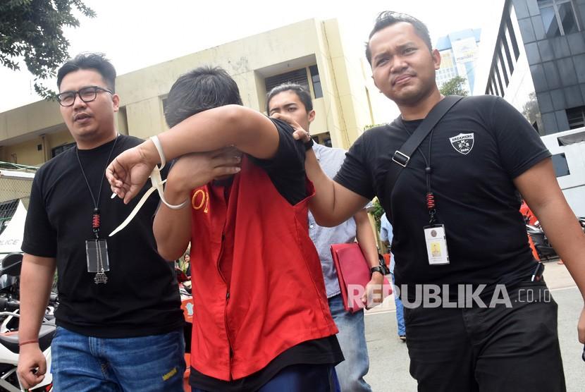 Polisi mengamankan tersangka penyebar hoaks atau berita bohong tujuh kontainer surat suara tercoblos, berinisial MIK (tengah) seusai konferensi pers terkait penangkapan pelaku di Polda Metro Jaya, Jumat (11/1/2019).