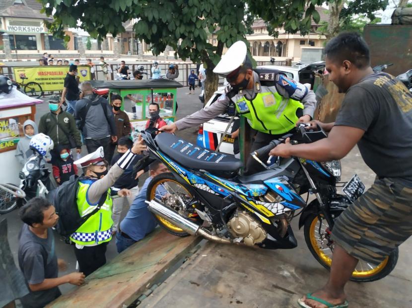 Polisi mengangkut kendaraan yang tak dilengkapi surat-surat ke atas truk tronton di Jalan Letnan Jenderal Mashudi, Kecamatan Cibeureum, Kota Tasikmalaya, Jumat (16/4). Terdapat ratusan kendaraan yang disita dari operasi itu.