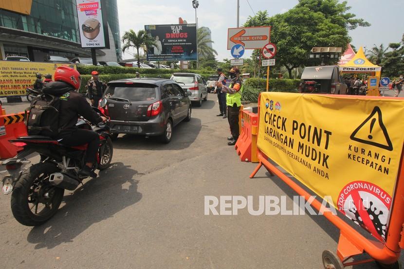 Polisi mengarahkan pengendara motor untuk melewati jalur yang benar saat simulasi penyekatan larangan mudik.