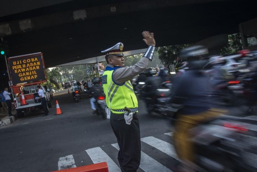 Polisi mengatur arus lalu lintas pada hari pertama uji coba perluasan kawasan ganjil genap di persimpangan Pancoran, Jakarta, Senin (2/7).