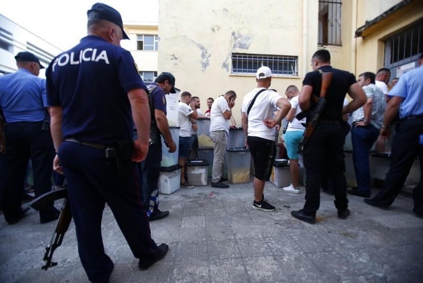 Polisi mengawal panitia pemilihan daerah yang antre mengantar surat suara di pusat penghitungan suara di Shkoder, Albania Utara, Ahad (30/6).