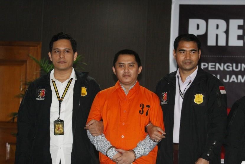 Polisi mengawal tersangka kasus penipuan PT First Travel Andika Surachman (tengah) saat gelar perkara kasus penipuan PT First Travel di Bareskrim Polri, Jakarta, Selasa (22/8).