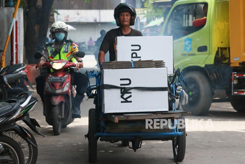 Polisi mengawal tukang becak yang mengangkut logistik hasil Pemilu 2019 di Jalan Tambak Sari, Surabaya, Jawa Timur, Kamis (18/4/2019).