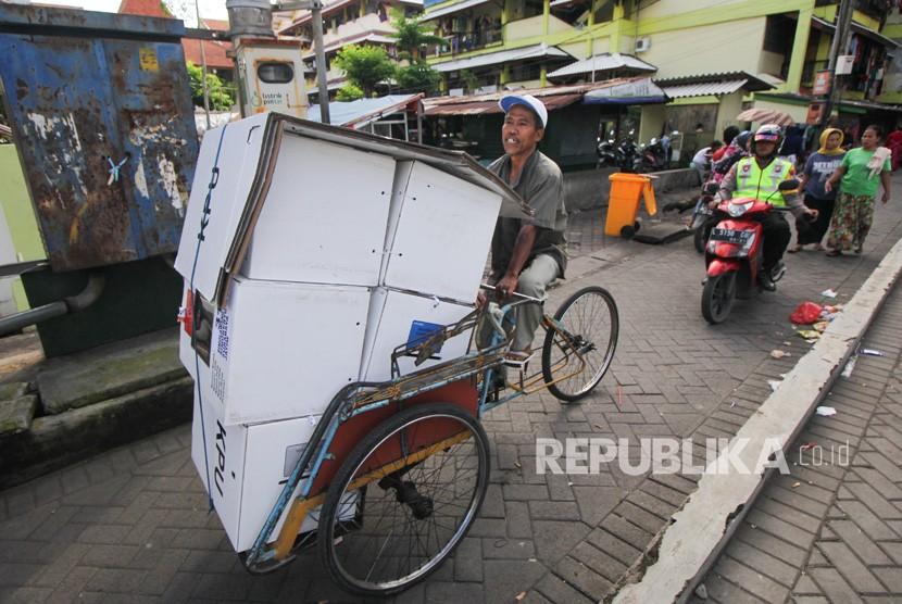 Polisi mengawal tukang becak yang mengangkut logistik hasil Pemilu 2019 di Rusun Sumbo, Surabaya, Jawa Timur, Kamis (18/4/2019).