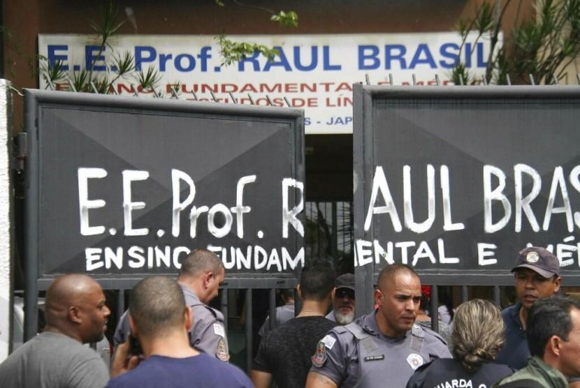 Polisi menjaga pintu masuk sekolah Raul Brasil State School di Suzano, Brasil, Rabu (13/3), setelah terjadi penembakan massal di sekolah tersebut.