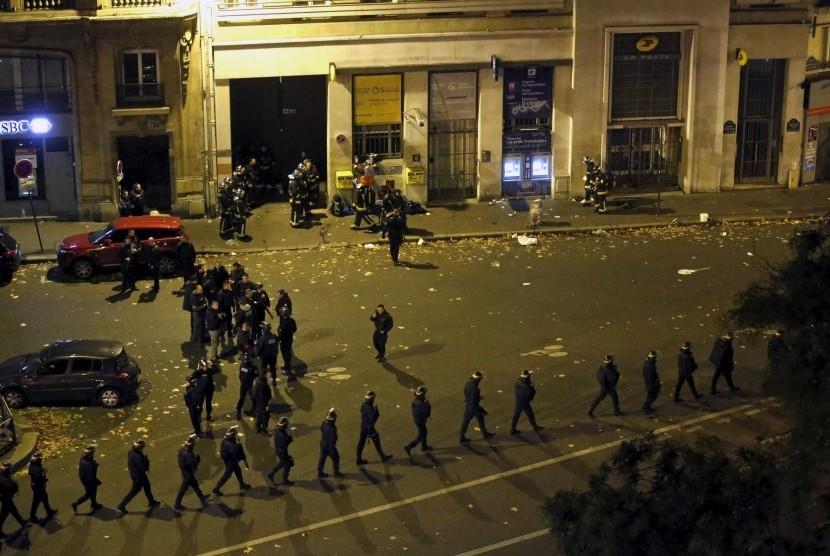Polisi Prancis mengenakan tameng berbaris di dekat Bataclan Concert Hall, area tempat salah satu insiden penembakan dan pengeboman terjadi di Paris, Prancis, Sabtu (14/11).