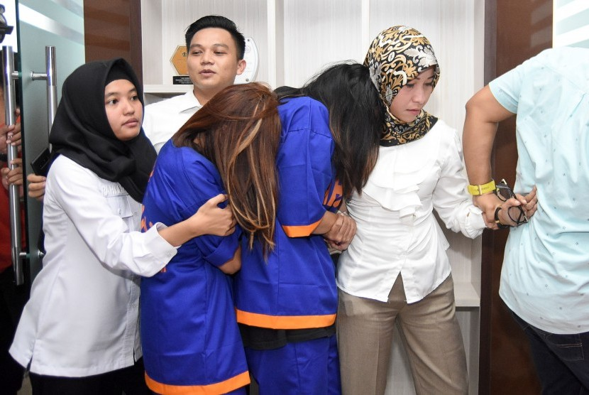 Two alleged pimps of online prostitution involving celebrities, ES and TN, escorted by policewomen during a press conference at East Java Police headquarters, Surabaya, Thursday (Jan 10).