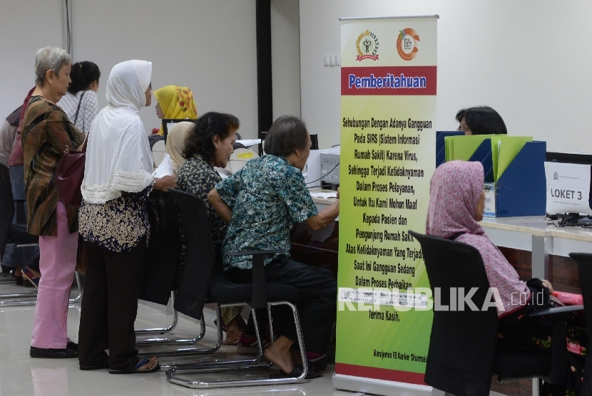 Poster pemberitahuan adanya gangguan pada Sistem Informasi Rumah Sakit (SIRS) karena virus terpasang di area pelayanan administrasi Rumah Sakit Kanker Dharmais, Jakarta, Senin (15/5).