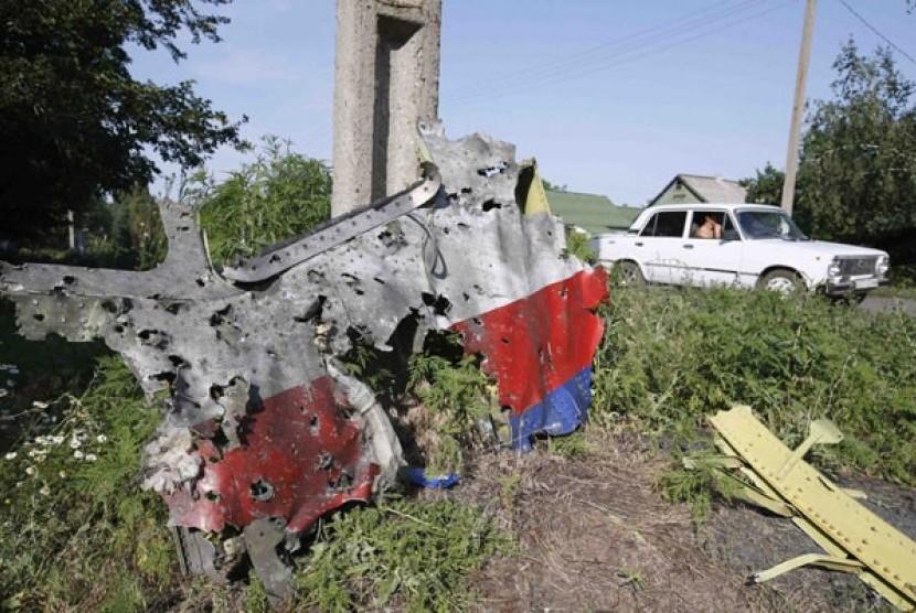 Potongan bangkai pesawat Malaysia Airlines MH17 yang jatuh ditembak terlihat di desa Petropavlivka, Donetsk, Ukraina, Kamis (24/7).
