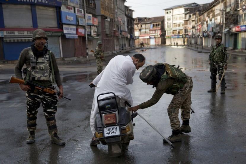 Prajurit Paramiliter India memeriksa tas seorang pria yang mengendarai skuter saat jam malam di Srinagar, Kashmir yang dikuasai India, Kamis (8/8).