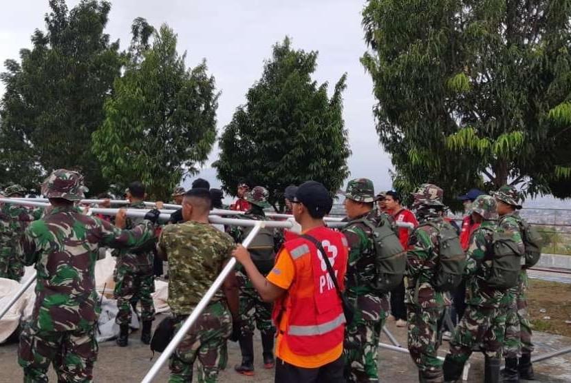 Prajurit TNI bersama dengan Palang Merah Indonesia (PMI) dan relawan membangun hunian sementara di wilayah Balaroa, Palu Barat, Palu, Sulawesi Tengah (Sulteng), Sabtu (13/10).