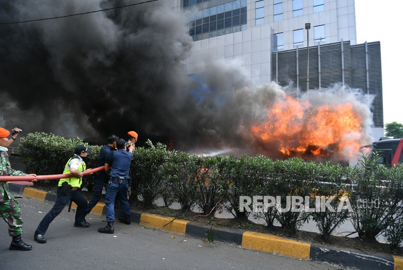 Prajurit TNI bersama warga mencoba memadamkan api yang membakar bus milik Brimob di kawasan Slipi, Jakarta Barat, Rabu (22/5/2019).