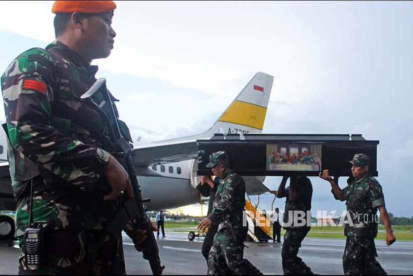 Prajurit TNI dan Polri mengusung peti jenazah korban KKB di Bandara Moses Kilangin Timika, Mimika, Papua, Jumat (7/12)