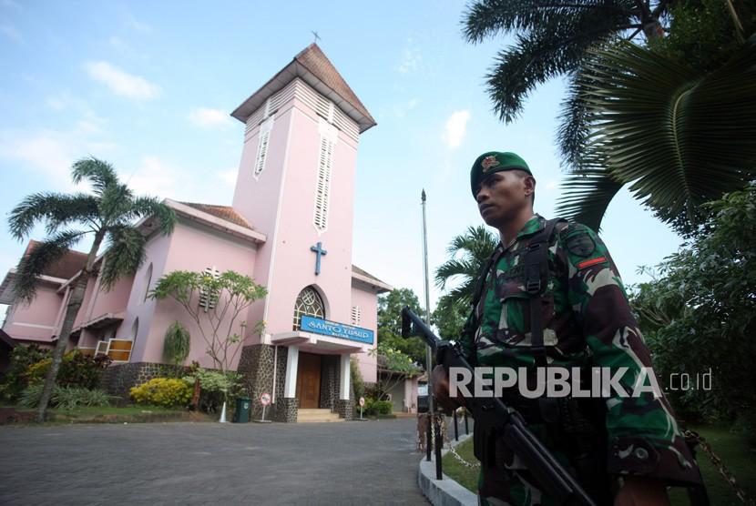 Prajurit TNI dari Bataliyon 511 berjaga di salah satu gereja katolik di Blitar, Jawa Timur, Ahad (13/5).