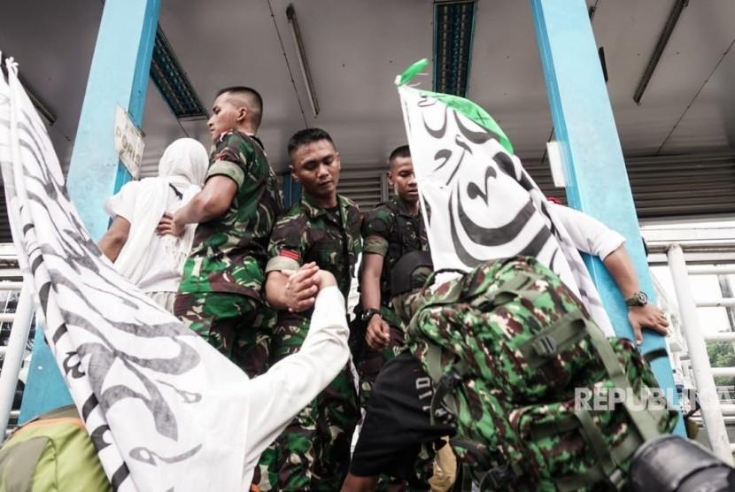 Prajurit TNI membantu peserta kegiatan Reuni 212 yang hendak menyeberang ke Stasiun Juanda, Jakarta Pusat, dari Masjid Istiqlal, Jakarta Pusat, Ahad (2/12). Peserta kegiatan Reuni 212 harus melompat ke halte bus Transjakarta untuk bisa cepat sampai ke Stasiun Juanda.