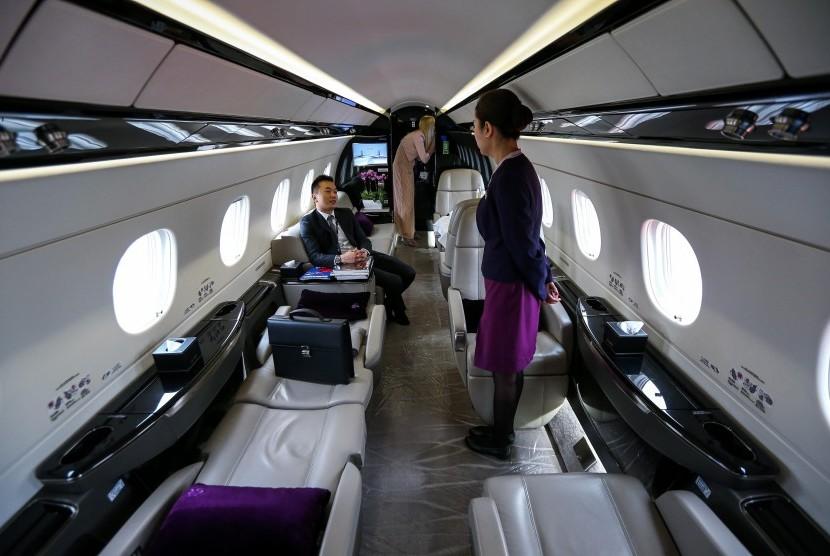 Pramugari berbincang dengan penumpang di pesawat.