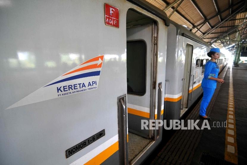 Pramugari mengarahkan penumpang di Stasiun Gambir.