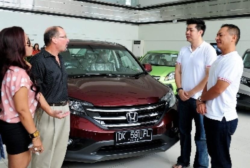 Presdir PT Honda Prospect Motor (HPM) Tomoki Uchida (kanan) bersama Direktur Pemasaran dan Layanan Purnajual Jonfis Fandy (dua kanan) berbincang dengan pembeli